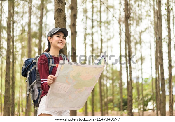 asian young woman hiker with a backpack walks through pine forest.