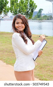 Asian young woman holding clapboard file with pen in hand look forward