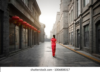 Asian young woman in old traditional Chinese dresses in Hutong village in Beijing, China. Woman walking to sight seeing in Beijing.
