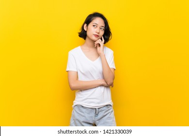 Asian young woman over isolated yellow wall thinking an idea while looking up