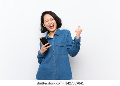 Asian young woman over isolated white background with phone in victory position