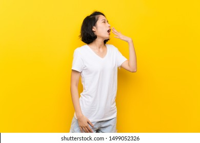 Asian young woman over isolated yellow wall yawning and covering wide open mouth with hand
