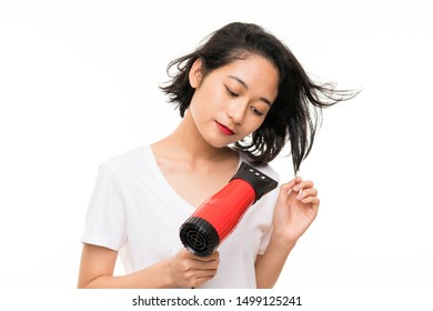 Asian young woman over isolated background with hairdryer