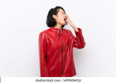 Asian young woman over isolated white background yawning and covering wide open mouth with hand