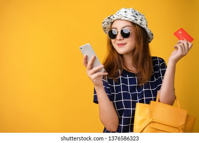 Asian young woman portrait in sunglasses holding credit card and bags, Shopping mid-year sale concept isolated on yellow background with copy space banner.