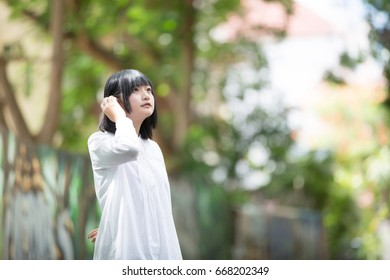 Asian young woman portrait with the tree background