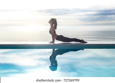 Asian young woman practice Cobra Pose on the pool above the beach in the morning,Feeling so comfortable and relax in holiday,Healthy Concept