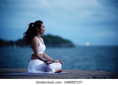 Asian young woman practicing yoga in sukhasana exercise while looking out to the sea.