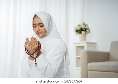 asian young woman praying with Al-Qur'an and prayer beads in white traditional clothes