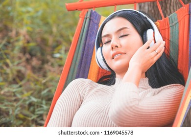 Asian young woman relax and listening music with headphone in the nature green park, happy time.