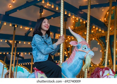 an asian young woman is riding roundabout in the theme park and enjoying a happy moment