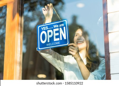 Asian young asian woman setting open sign at the shop glasses for welcome the customer in to the coffee shop, small business owner and startup with cafe shop, installing open and close label concept