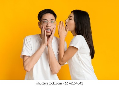 Asian young woman sharing shocking news with her boyfriend over yellow studio background