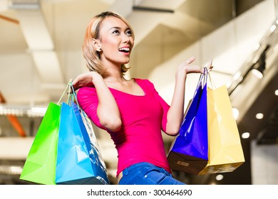 Asian young woman shopping fashion in store with lots of bags over her shoulders