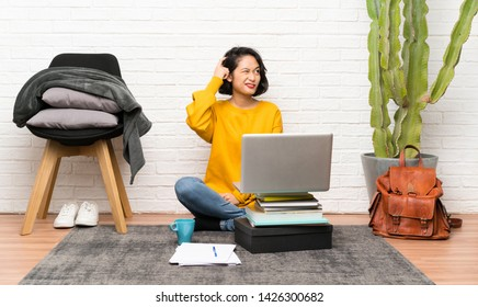 Asian young woman sitting on the floor having doubts and with confuse face expression