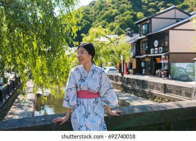 an asian young woman smiling and wearing Yukata, Japanese traditional clothes, in old town