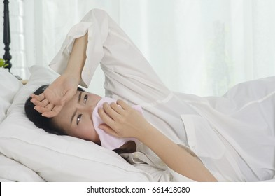 asian young woman sneezing in a handkerchief on bed.