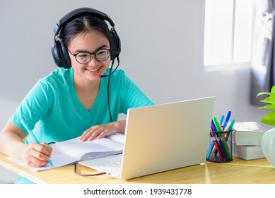 Asian young woman student with glasses headphones girl study happy writing note on a book looking video conference laptop computer university class online internet learning distance education at home