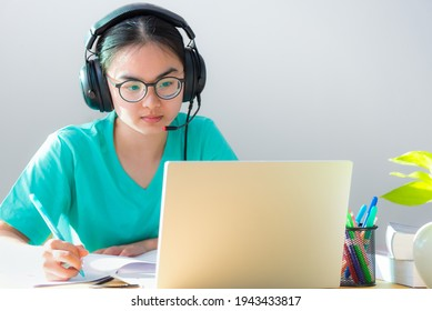 Asian young woman student with glasses headphones study serious writing note on a book looking video conference on laptop computer university class online internet learning distance education at home