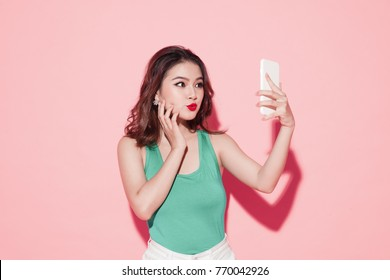 Asian young woman taking selfie photo on pink background.
