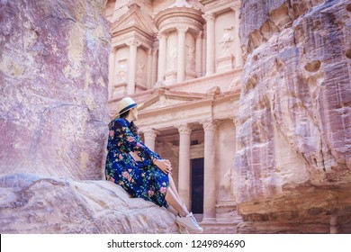 Asian young woman tourist in color dress and hat enjoying the Treasury, Al Khazneh in the ancient city of Petra, Jordan, UNESCO World Heritage Site