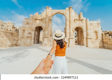 Asian young woman tourist in color dress and hat leading man to South gate of the Ancient Roman city of Gerasa, modern Jerash, Jordan. Traveling together. Follow me.