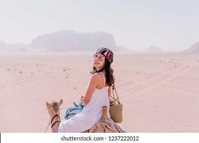 Asian young woman tourist in white dress riding on camel in wadi rum desert, Jordan