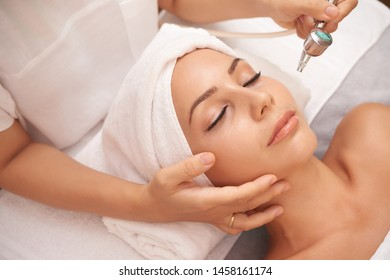 Asian young woman with towel on her head lying with her eyes closed and relaxing during procedure at cosmetological cabinet