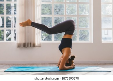 Asian young woman training yoga doing headstand pose on floor in room in morning. Instructor woman leading exercise pose, Healthy lifestyle, working out, indoor full length, studio background.
