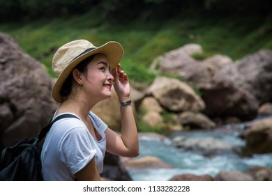 Asian young woman traveler travel and relax at the peak mountain or green forest with mountain river or water stream