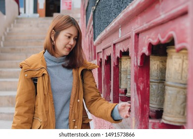 Asian young woman traveler in yellow jacket rotating praying wheels for religious reason at Thiksey monastery in ladakh, northern india.