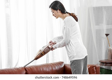 Asian young woman use vacuum cleaner to clean sofa