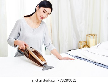Asian young woman uses a vacuum cleaner to clean mites in the sheets