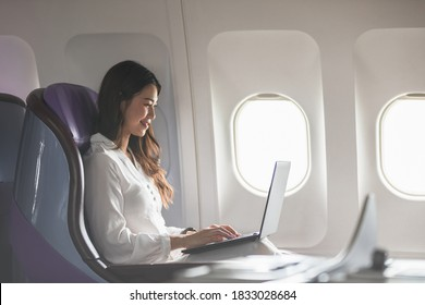 Asian young woman using laptop sitting near windows at first class on airplane during flight,Traveling and Business concept