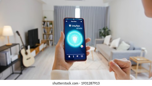 Asian young woman is using smart home app and touch screen to turn on the light by mobile phone