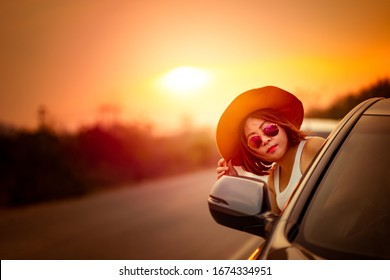 Asian young woman wear hat and sunglasses popping head out the car window with sunset background. Road trip vacation, white Caucasian woman.
