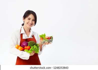 Asian young woman wearing an apron coat and holding fresh ingredients for healthy salad.