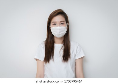 Asian Young woman in a white t-shirt and wear medical mask that protects against the spread of coronavirus or COVID-19 disease. Studio Portrait with White Background.