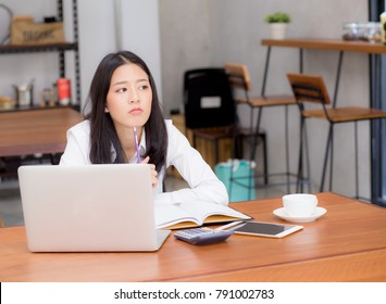 Asian young woman working online with laptop and think project for idea at modern cafe shop, business and freelance concept.