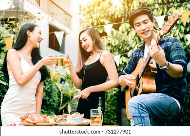 Asian young women enjoying toasting drinks party with guy playing guitar singing at home garden outdoors.