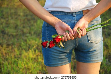Asian young women are fall in love. She hiding the red roses behind her back and standing in the evening sunshine on the blurred meadow background.