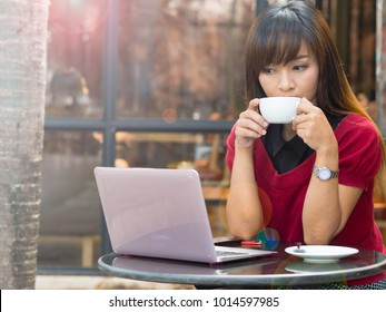 Asian young working and business woman sipping hot coffee latte from coffee cup and checking news and event on online social media in cafe on urban street at morning