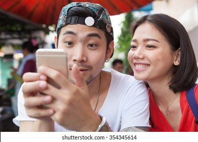 asian younger man and woman watching on smart phone with happy face