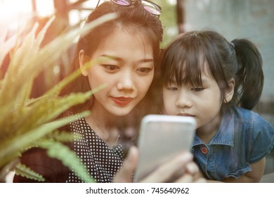 asian younger woman and children looking to smart phone screen at home living room