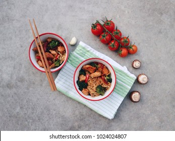Asian/Chinese/Thai noodles in a bowl with chicken and vegetables. Bowl on a green cloth, mushrooms and  tomatoes. Chopsticks. Traditional meal on a concrete stone background. Top view. Asian dinner