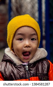 Asiand kid wearing a yellow wool cap, showing his tongue and posing in front of the camera. Hanoi, Vietnam. December 4, 2018