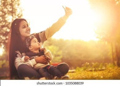 Asian/Indian beautiful Mother taking selfie with her smart-phone camera of her and her baby daughter. outdoor in nature.