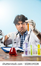 Asian/Indian male scientist or doctor or science student experimenting with microscope and chemicals, laptop and smartphone in a lab