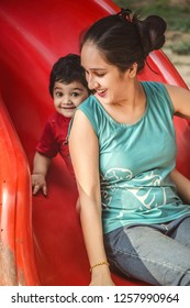Asian/Indian mother and daughter playing on slide in playground