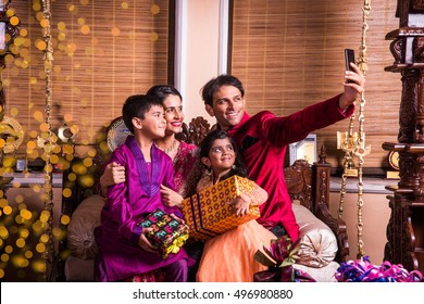 Asian/Indian young family taking selfie or self photograph at home with gift boxes on Diwali festival night.